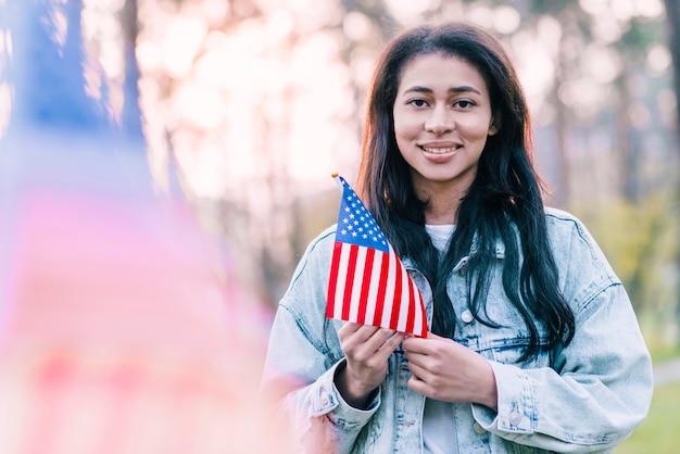 Schöne frau mit amerikanischer flagge der andenkens draußen Kostenlose Fotos