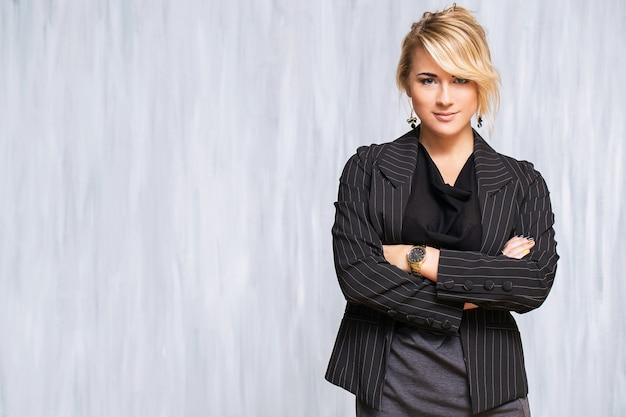 Schöne frau mit blonden haaren und schwarzem anzug Kostenlose Fotos