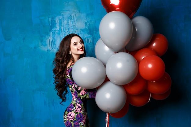 Schöne frau mit bunten luftballons im studio Premium Fotos