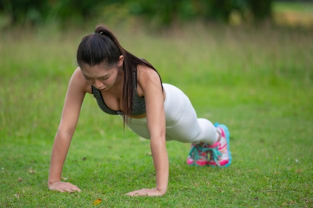 Schöne frau mit dem langen haar trainierend auf dem parkrasen. Kostenlose Fotos