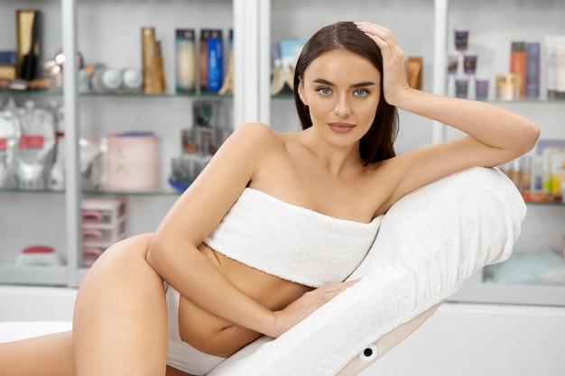 Schöne frau mit dem perfekten körper, der am spa in der weißen hose und in der büste sitzt, die durch handtuch bedeckt werden Premium Fotos