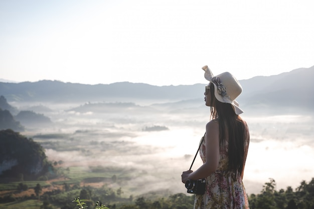 Schöne frau mit einer kamera, die auf der bergspitze steht Kostenlose Fotos