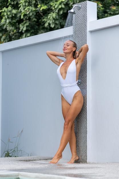 Schöne frau mit fitem körper in guter form, die entspannende dusche draußen in der villa nimmt tropenferienurlaub wasser fließt durch den körper des mädchens wasserspritzen Kostenlose Fotos
