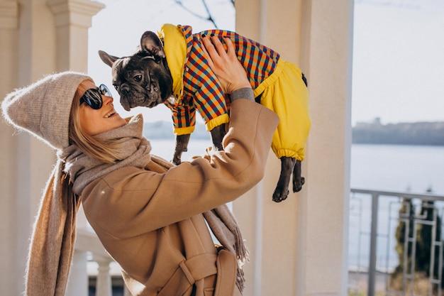 Schöne frau mit französischer bulldogge gehend in park Kostenlose Fotos