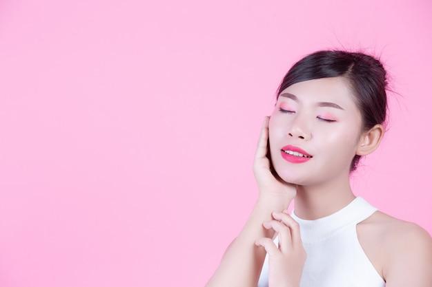 Schöne frau mit gesunder haut und schönheit auf einem rosa hintergrund. Kostenlose Fotos