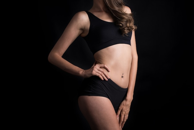 Schöne frau mit gesunder karosserie auf schwarzem hintergrund Kostenlose Fotos