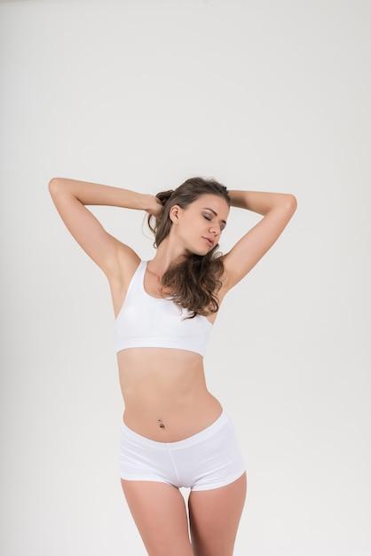 Schöne frau mit gesunder karosserie auf weißem hintergrund Kostenlose Fotos