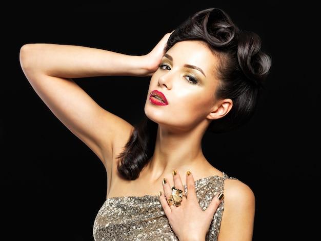 Schöne frau mit goldenen nägeln und mode make-up der augen. brunet mädchen modell mit stil frisur auf schwarzer wand Kostenlose Fotos
