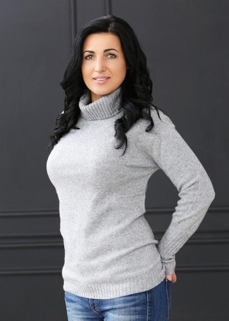 Schöne frau mit grauem pullover und jeans Kostenlose Fotos