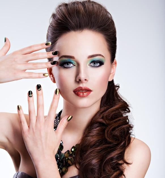 Schöne frau mit grünem make-up und kreativer farbe der nägel Kostenlose Fotos