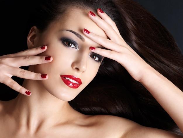 Schöne frau mit langen braunen geraden haaren und roten nägeln, die auf der dunklen wand liegen Kostenlose Fotos