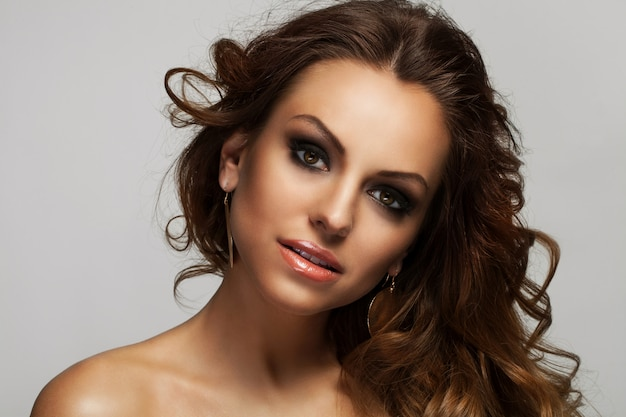 Schöne frau mit locken und make-up Kostenlose Fotos