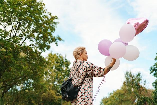 Schöne frau mit rucksack, der glücklich mit rosa luftballons im park geht. konzept für freiheit und gesunde frauen. Kostenlose Fotos