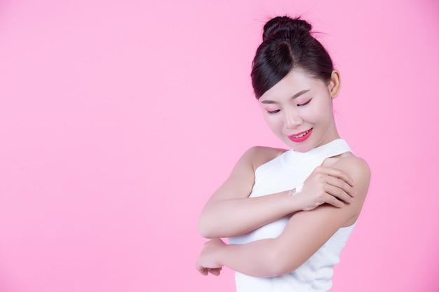 Schöne frau mit sahne auf der haut auf einem rosa hintergrund. Kostenlose Fotos