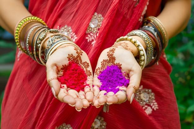Schöne frau tragen traditionelles rotes sari-kleid der indischen hochzeit halten in händen mit henna-tätowierung und armbändern bunte rosa violette holi-staubpulverfarbe. frohe feiertags-sommerkulturfestival-konzept Premium Fotos