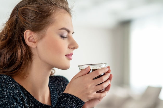 Schöne frau trinkt kaffee und genießt den geschmack. hübsches junges erwachsenes mädchen, das mit tasse tee entspannt. Kostenlose Fotos
