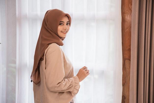 Schöne frau verschleiert stehend nahe vorhang, der zurück schaut und lächelt Premium Fotos