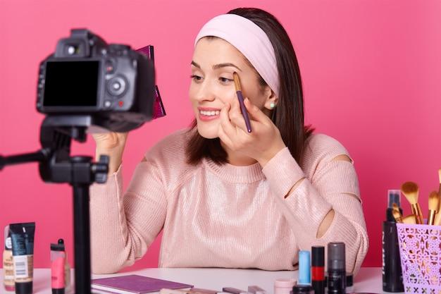 Schöne frau zeichnet video auf. yong blogger zeigt, wie man lidschatten aufträgt. lady berät kosmetik auf ihrem kanal Premium Fotos