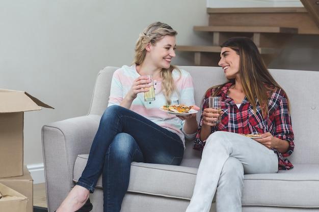 Schöne frau zwei, die auf sofa sitzt und pizza isst Premium Fotos