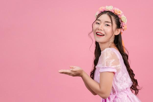 Schöne frauen, die in schönen rosa prinzessinkleidern gekleidet sind, stehen auf einem rosa. Kostenlose Fotos