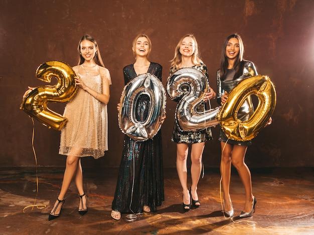 Schöne frauen, die neues jahr feiern. glückliche herrliche mädchen in den stilvollen sexy party-kleidern, welche die gold- und silber-2020-ballone, spaß an der sylvesterparty habend halten. holiday celebration.charming models Kostenlose Fotos