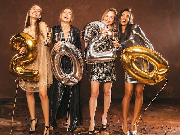 Schöne frauen, die neues jahr feiern. glückliche herrliche mädchen in den stilvollen sexy party-kleidern Kostenlose Fotos