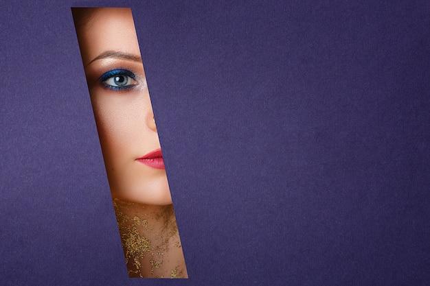 Schöne frauenaugen schauen in das papierloch, helles make-up. Premium Fotos