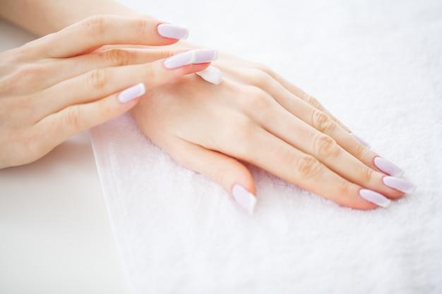 Schöne frauenhände mit perfekter maniküre tragen sie creme auf die hauthände auf, Premium Fotos