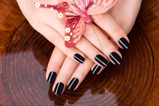Schöne frauenhände mit schwarzer maniküre nach spa-eingriffen - spa-behandlungskonzept Kostenlose Fotos
