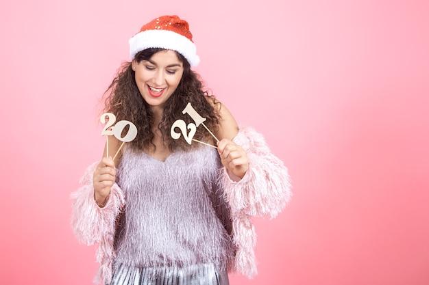Schöne freudige junge brünette frau mit lockigem haar in einer weihnachtsmütze auf einem rosa hintergrund, der eine hölzerne zahl für das neujahrskonzept hält Kostenlose Fotos