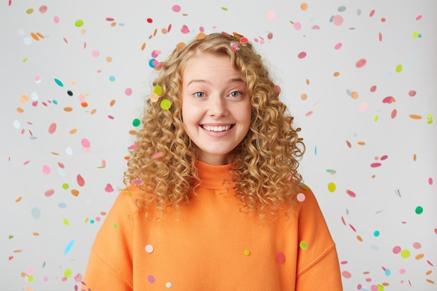 Schöne freudige schön nette blauäugige blondine steht unter fallendem konfetti lächelnd zeigt gesunde zähne Kostenlose Fotos