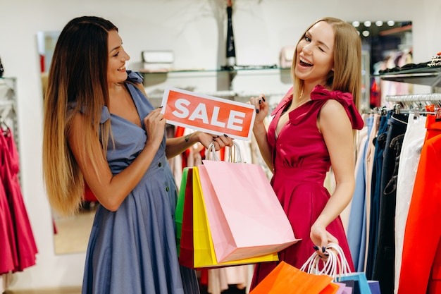 Schöne freundinnen in geschäften kauften kleidung zu ermäßigten preisen Premium Fotos