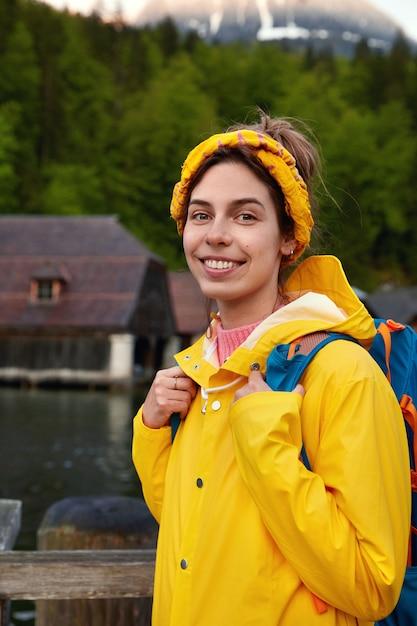 Schöne fröhliche dame mit angenehmem lächeln, trägt gelben regenmantel mit kapuze, trägt rucksack Kostenlose Fotos