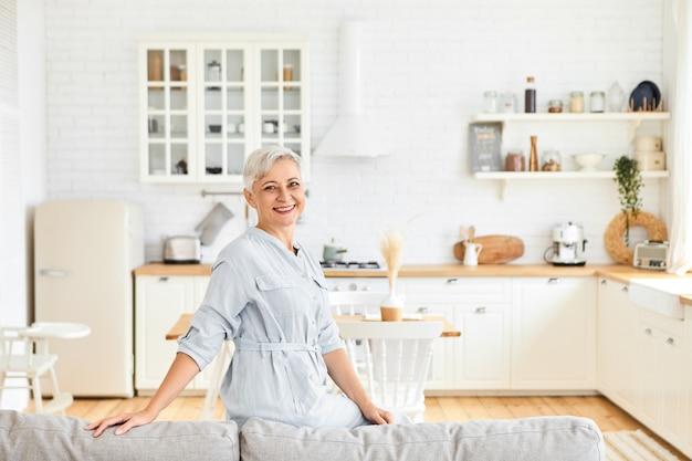 Schöne fröhliche kaukasische hausfrau im eleganten kleid posiert im wohnzimmer, sitzt auf der rückseite der großen grauen couch, lächelt und zeigt ihnen ihre geräumige gemütliche wohnung. ältere menschen und lebensstil Kostenlose Fotos