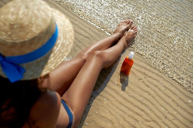 Schöne, gepflegte frauenbeine mit einer creme zum schutz vor sonnenbrand Premium Fotos