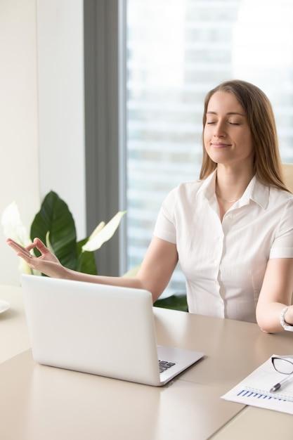 Schöne geschäftsfrau, die im büro meditiert Kostenlose Fotos
