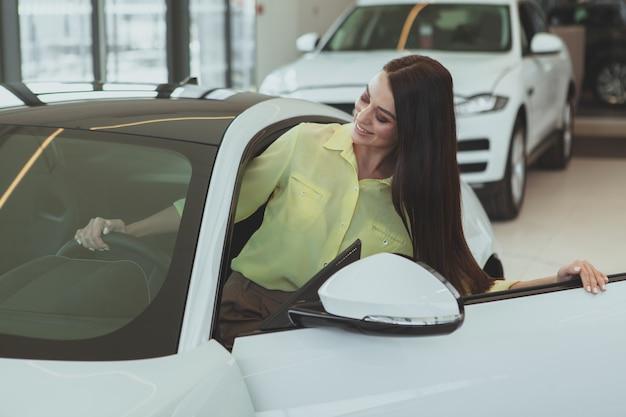 Schöne geschäftsfrau, die neues automobil kauft Premium Fotos