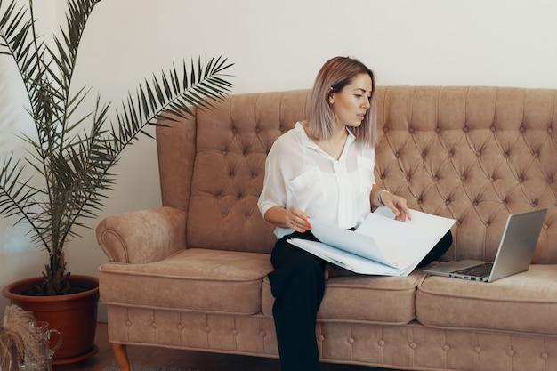 Schöne geschäftsfrau, die zu hause arbeitet. multitasking-, freiberufler- und mutterschaftskonzept Kostenlose Fotos
