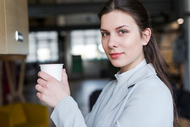 Schöne geschäftsfrau, welche die wegwerfkaffeetasse betrachtet kamera hält Kostenlose Fotos