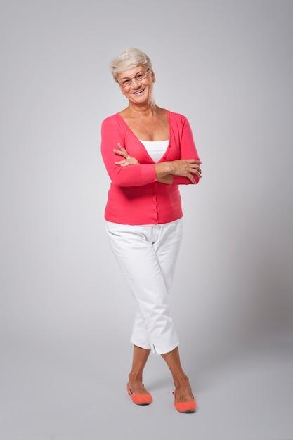 Schöne glückliche ältere frau, die modekleidung trägt