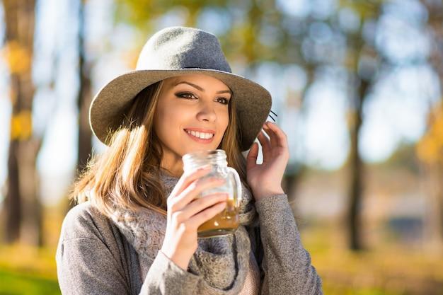 Schöne glückliche blonde junge frau in der grauen jacke und im hut Premium Fotos