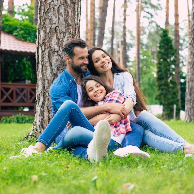 Schöne glückliche familie beim zusammensitzen auf dem rasen Premium Fotos