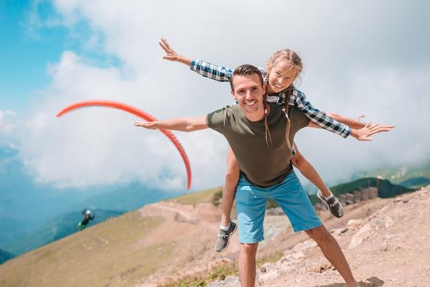 Schöne glückliche familie in den bergen im hintergrund des nebels Premium Fotos