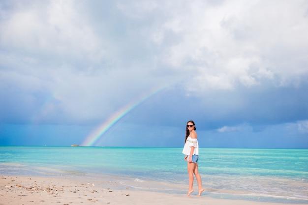 Schöne glückliche frau am strand mit schönen regenbogen über dem meer Premium Fotos