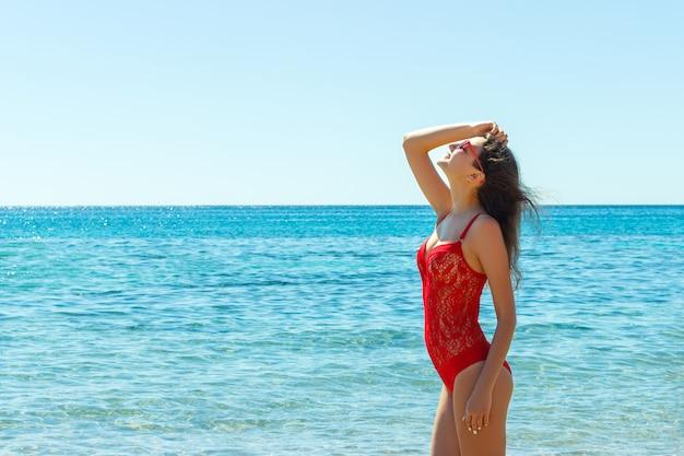 Schöne glückliche frau am tropischen strand im badeanzug und in den sunglassses Premium Fotos