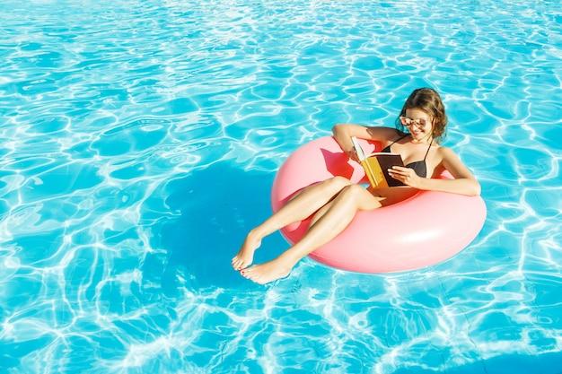 Schöne glückliche frau, die ein buch mit dem aufblasbaren ring sich entspannt im blauen swimmingpool liest Premium Fotos