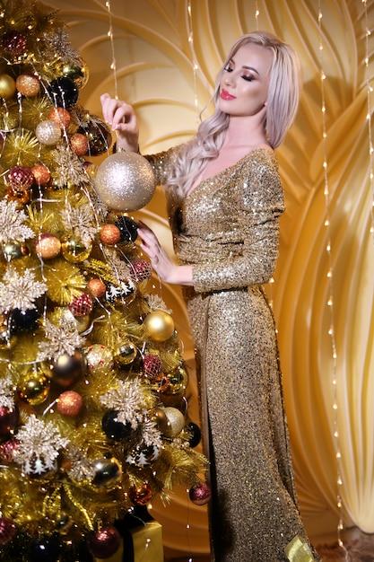 Schöne glückliche frau mit goldener kugel Premium Fotos