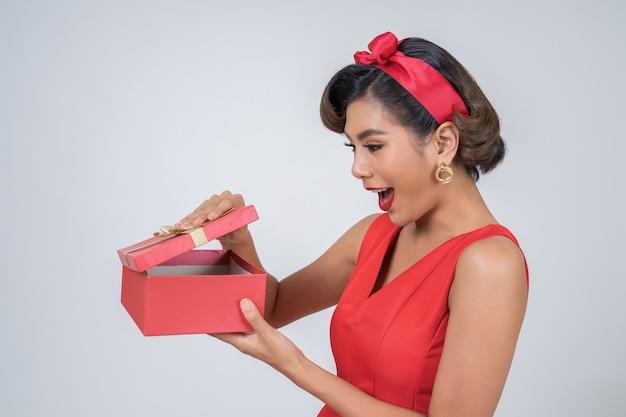 Schöne glückliche frau mit überraschungsgeschenkbox Kostenlose Fotos