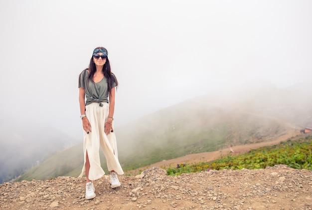 Schöne glückliche junge frau in den bergen im hintergrund des nebels Premium Fotos