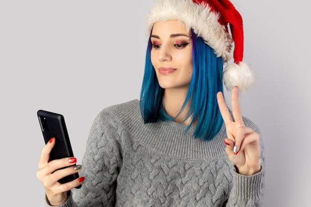 Schöne glückliche junge frau in der weihnachtsmütze nehmen selfie. weihnachts-neujahrsfeierkonzept Premium Fotos